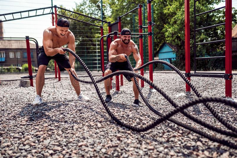 Men work hard with rope at street gym yard. Strength and motivation. Outdoor workout. fitness, sport, exercising stock photography