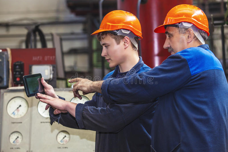 Men work on the old factory for the installation of equipment stock photography