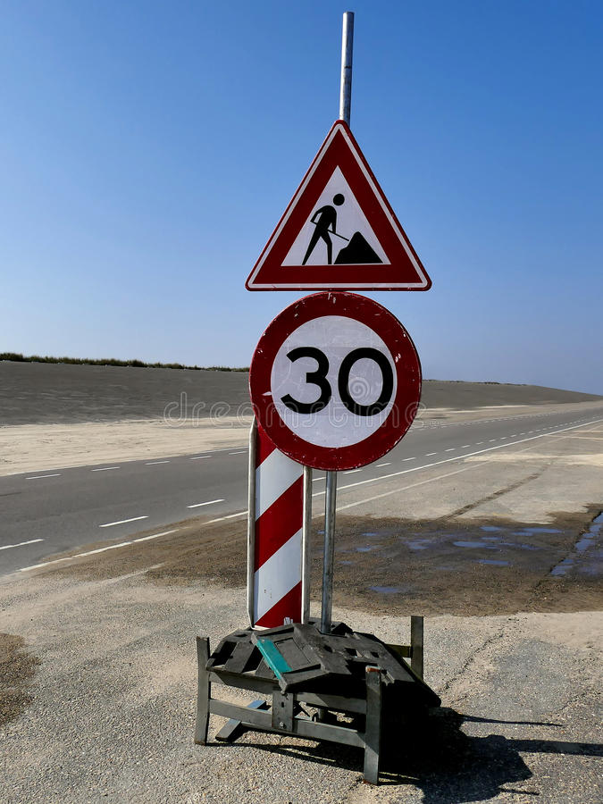 Men at work sign on empty road. Caution to drive slow. royalty free stock images