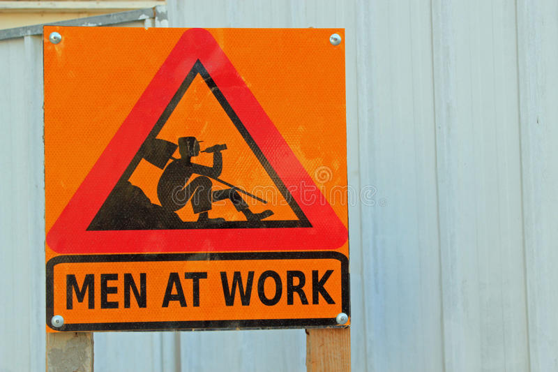 Men at Work sign. Red warning triangle on a yellow background with picture of a workman with a shovel over his shoulder and the words Men at Work symbolizing royalty free stock images