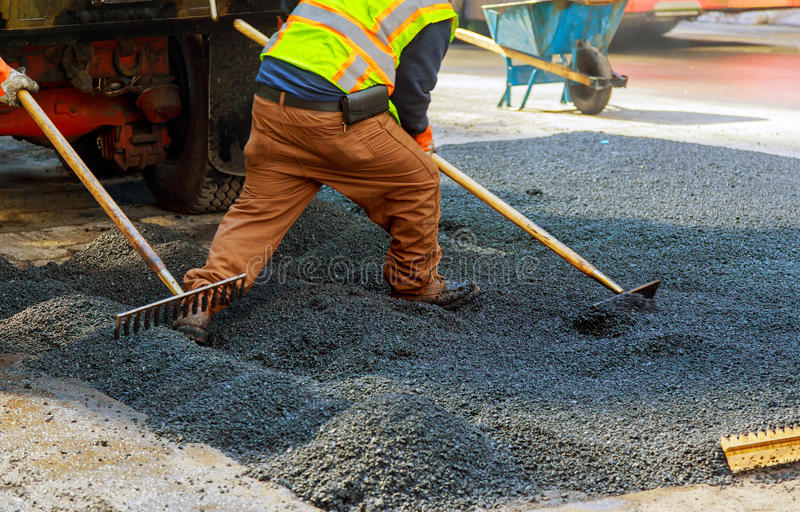 Men at work, urban road under construction, asphalting in progress. Workers install sewer manhole stock photography