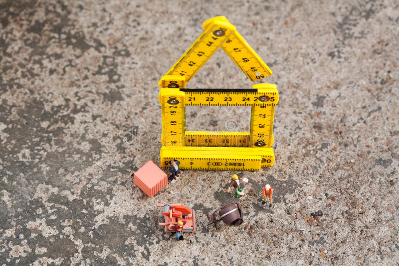 Men working on a building site. Overhead view of tiny miniature men working on a building site with miniature equipment on a house frame composed of a yellow royalty free stock images