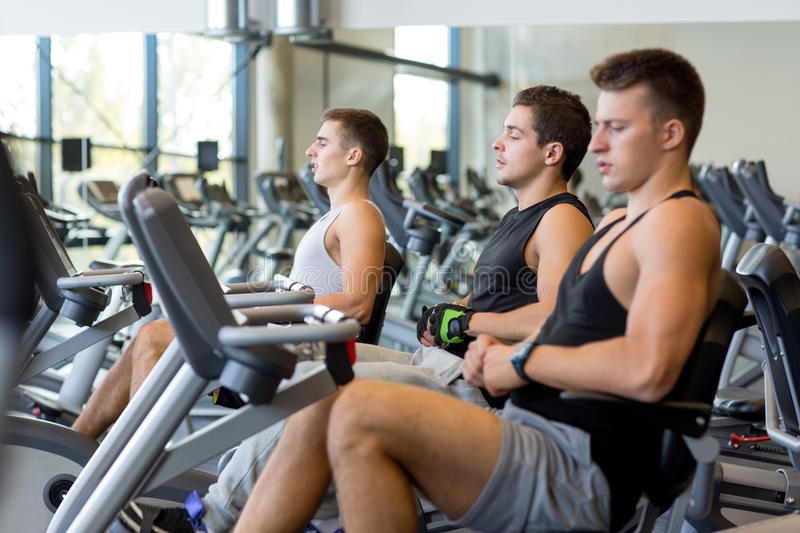 Men working out on exercise bike in gym stock photo