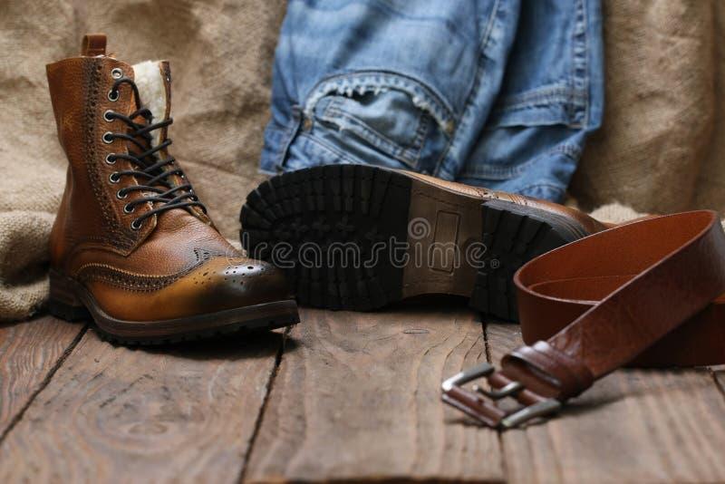 Men& x27; zapatos de s, vaqueros, correa de cuero en un fondo del tablón de madera imágenes de archivo libres de regalías