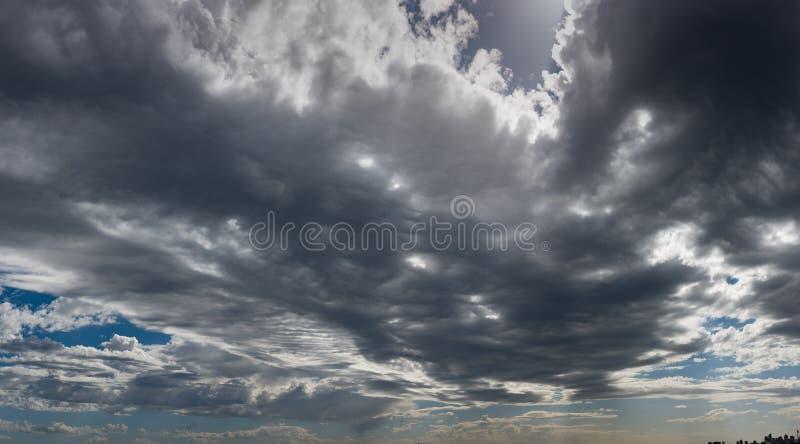 Menacing dark clouds with horizon panorama. Menacing dark clouds panoramic view with perspective towards horizon. Dark grey, white and blue sky in focus royalty free stock photos