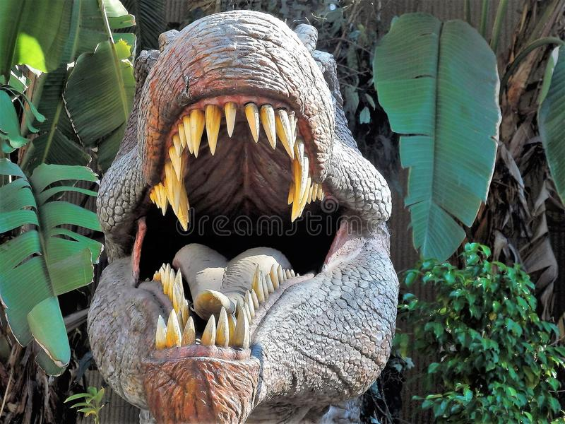 Menacing dinosaur Jaws. Jutting out from the green forest stock photography