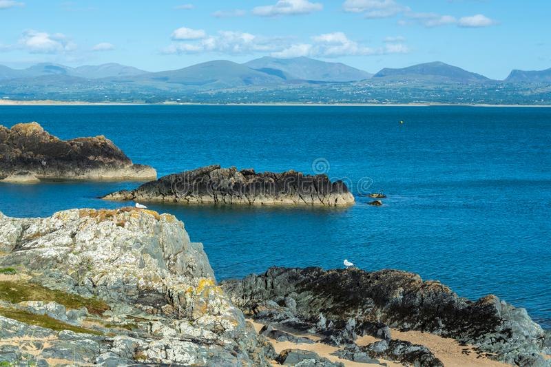 Menai Strait and Snowdonia mountains seen from rocky coast of Anglesey Island - 2. Menai Strait and Snowdonia mountains seen from rocky coast of Anglesey Island royalty free stock photography