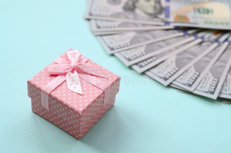 Menchia kropkujący prezenta pudełko kłama blisko sto dolarowych rachunków na bławym tle zdjęcie stock