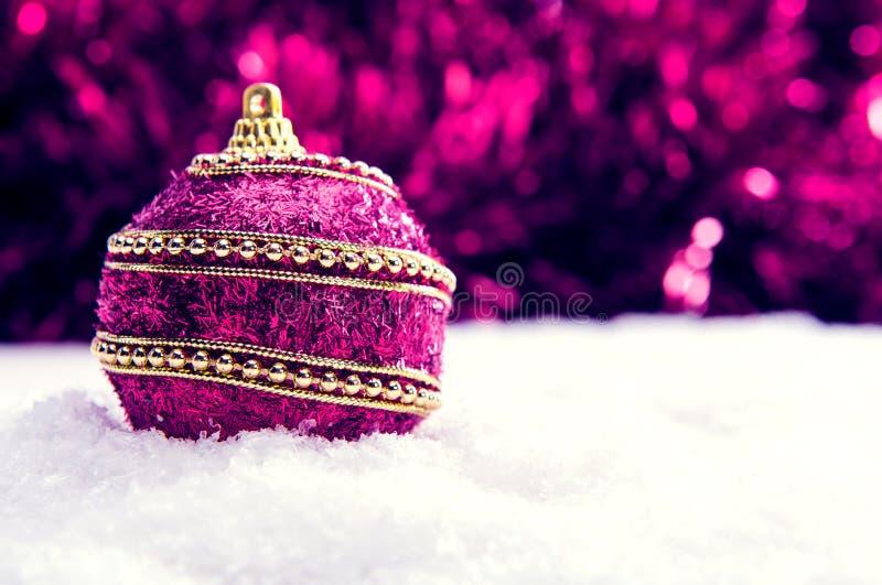 Menchie i Bożenarodzeniowa piłka w purpurowa i złocista śniegu i tinsle, bożego narodzenia tło fotografia royalty free