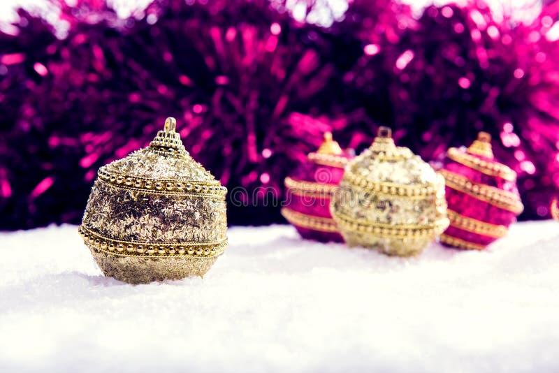 Menchie i Bożenarodzeniowe piłki w śniegu z świecidełkiem purpurowe i złociste, bożego narodzenia tło fotografia royalty free