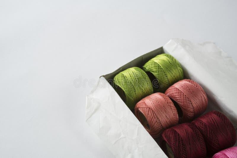 Menchii, czerwieni i zieleni szydełkowa przędza w pudełku na bielu stole, Przestrzeń dla teksta obrazy stock