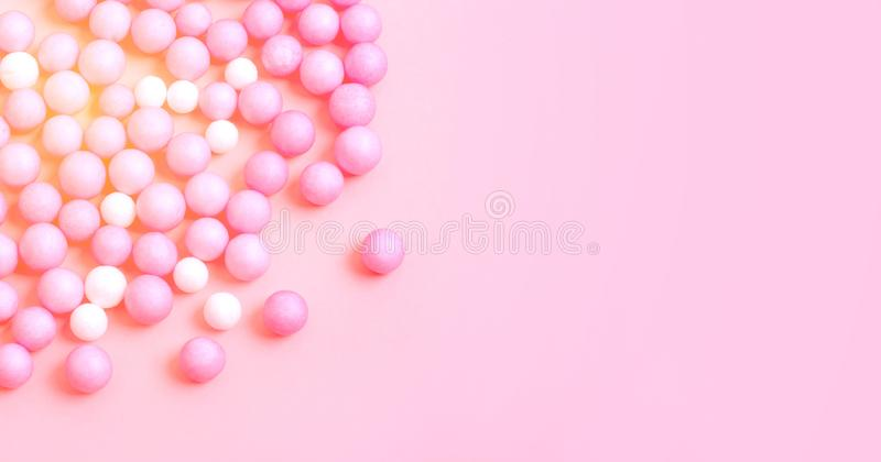 Menchii i białych małe piłki rozpraszają na różowią powierzchnię zdjęcie royalty free