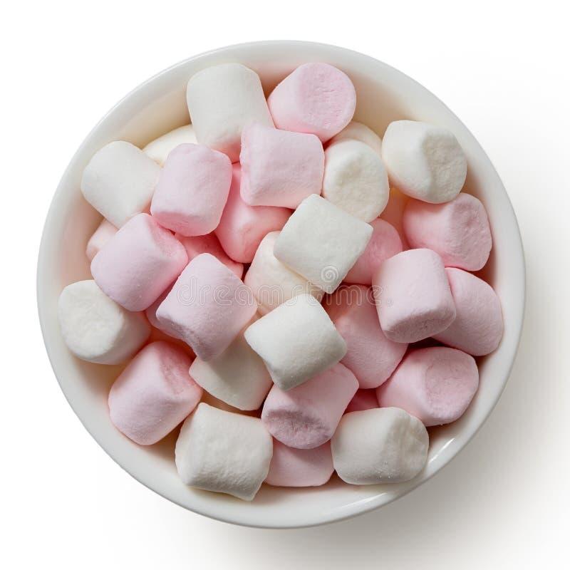 Menchii i białych mini marshmallows w białym ceramicznym naczyniu odizolowywającym na bielu z góry zdjęcie royalty free