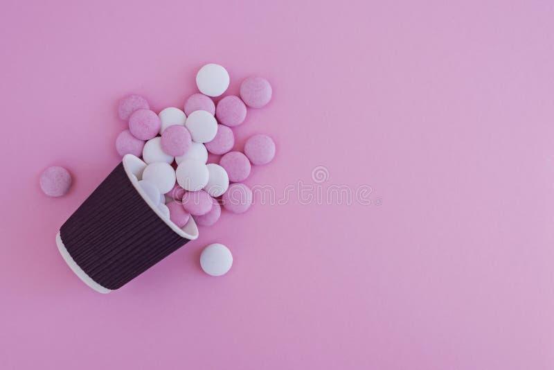 Menchii i białych round cukierki nalewali z filiżanki na różowym tle zdjęcia stock