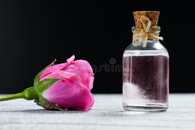 Menchii róży kwiat i szkło butelka istotny olej lub róży woda z różanymi płatkami fotografia royalty free