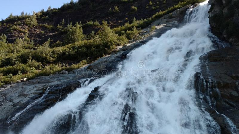 Mendenhall glaciär i Juneau Alaska Stor glaciär som glider in i en sjö med en vattenfall bredvid den Mycket populärt turist- stop arkivbilder
