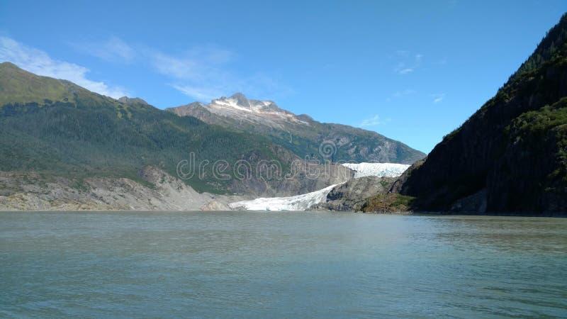 Mendenhall glaciär i Juneau Alaska Stor glaciär som glider in i en sjö med en vattenfall bredvid den Mycket populärt turist- stop arkivfoto
