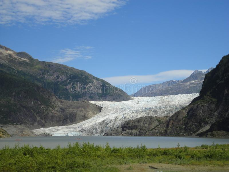 Mendenhall Glacier Juneau Alaska. Mendenhall Glacier flowing into Mendenhall Lake in between mountains with Nugget falls. Perfect royalty free stock photos