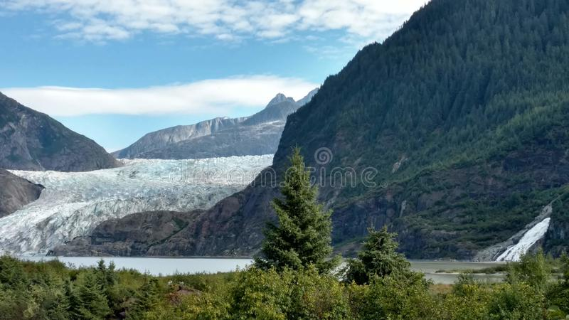 Mendenhall Glacier in Juneau Alaska. Large Glacier sliding into a lake with a waterfall beside it. Very popular tourist stop stock photo