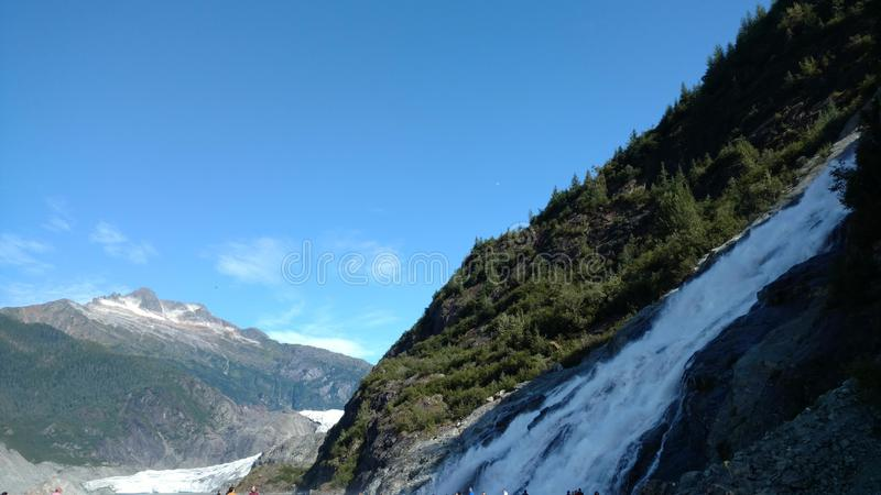 Mendenhall Glacier in Juneau Alaska. Large Glacier sliding into a lake with a waterfall beside it. Very popular tourist stop royalty free stock images