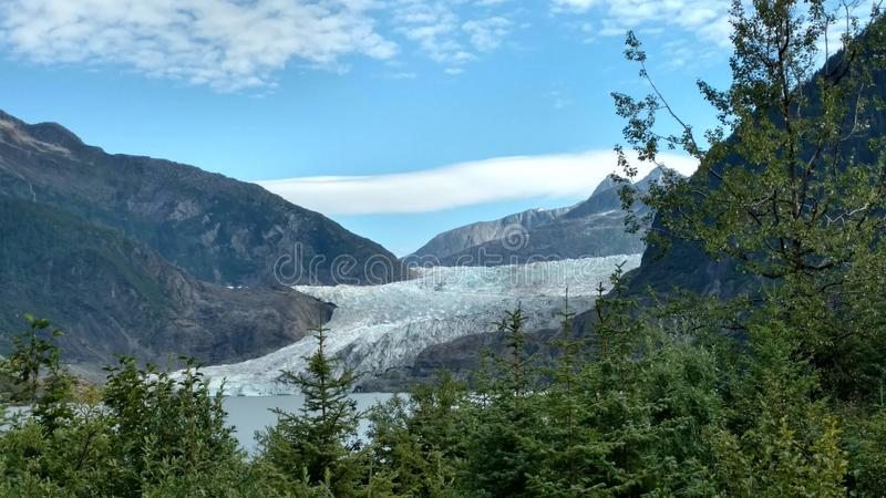 Mendenhall Glacier in Juneau Alaska. Large Glacier sliding into a lake with a waterfall beside it. Very popular tourist stop stock image