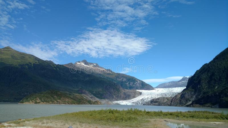 Mendenhall Glacier in Juneau Alaska. Large Glacier sliding into a lake with a waterfall beside it. Very popular tourist stop royalty free stock photography