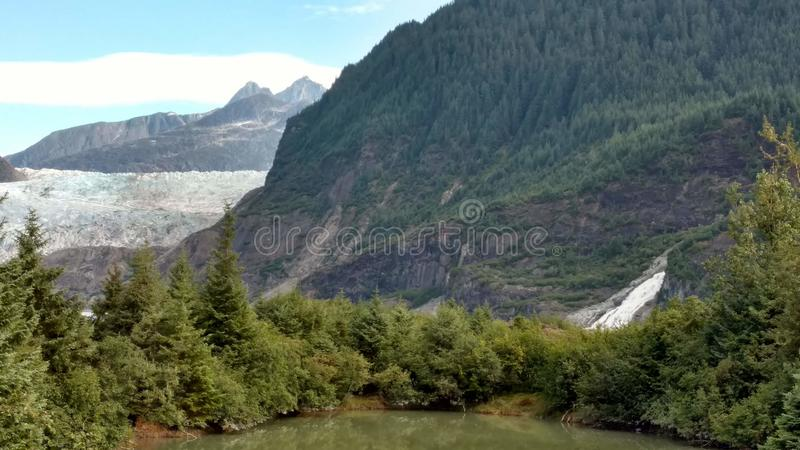 Mendenhall Glacier in Juneau Alaska. Large Glacier sliding into a lake with a waterfall beside it. Very popular tourist stop stock images