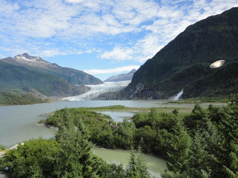 Mendenhall Glacier Juneau Alaska. Mendenhall Glacier flowing into Mendenhall Lake in between mountains with Nugget falls. Perfect stock photos