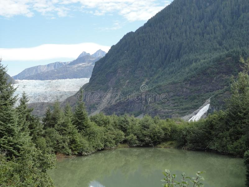 Mendenhall Glacier Juneau Alaska. Mendenhall Glacier flowing into Mendenhall Lake in between mountains with Nugget falls. Perfect stock photo