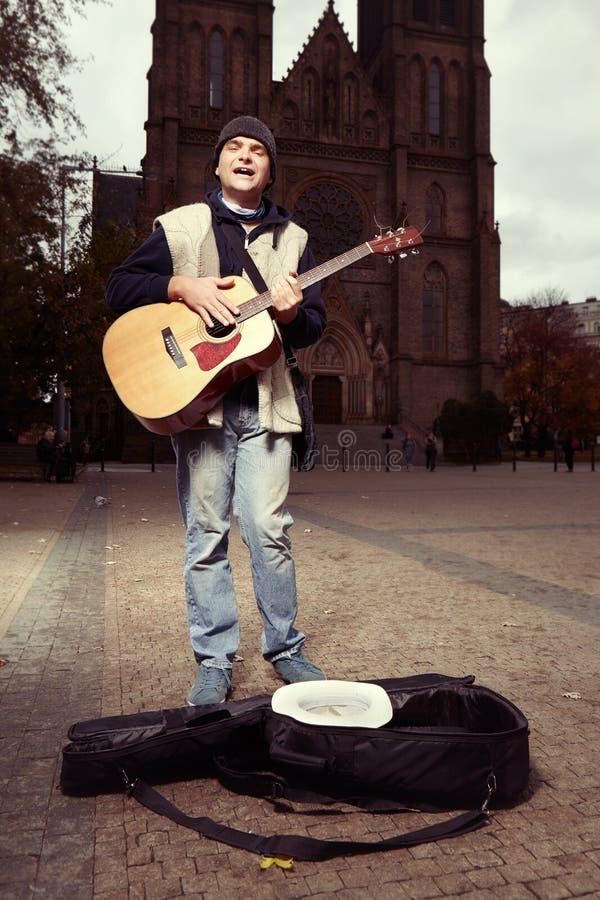 Mendiant avec la guitare essayant de gagner l'argent sur le public photo stock