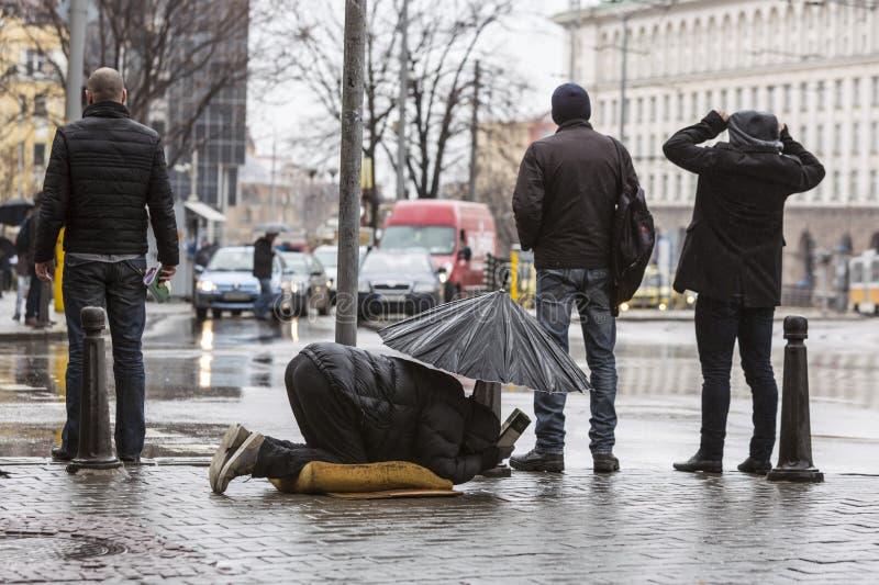 Mendiant sans abri avec le parapluie sous la pluie photo libre de droits