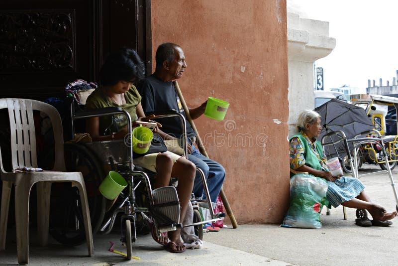 Mendiant sur le fauteuil roulant près de l'homme aveugle à l'aide du téléphone portable au portail de porte de porte d'église photos stock