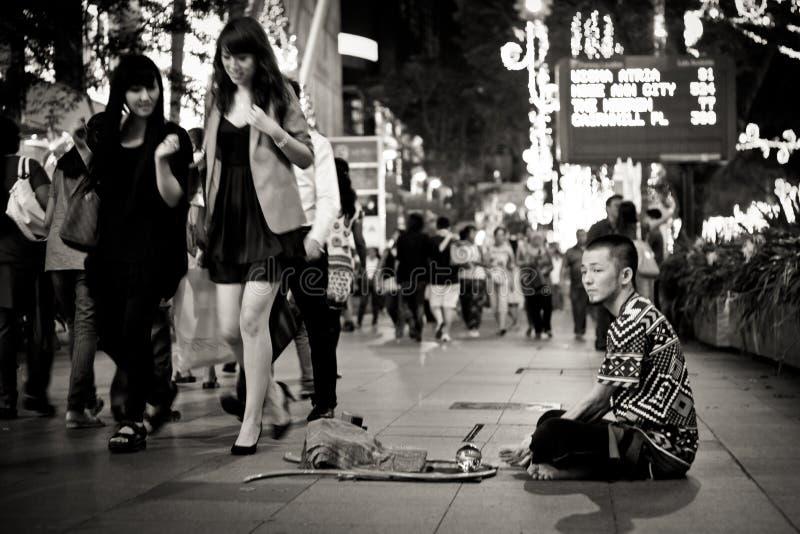 Mendicante e donna ricca in una zona commerciale a Singapore immagini stock libere da diritti