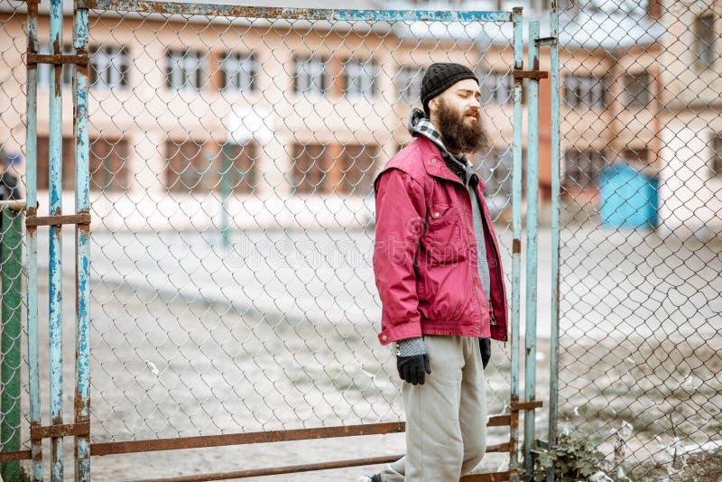 Mendicante o prigioniero vicino al vecchio recinto del metallo all'aperto fotografie stock