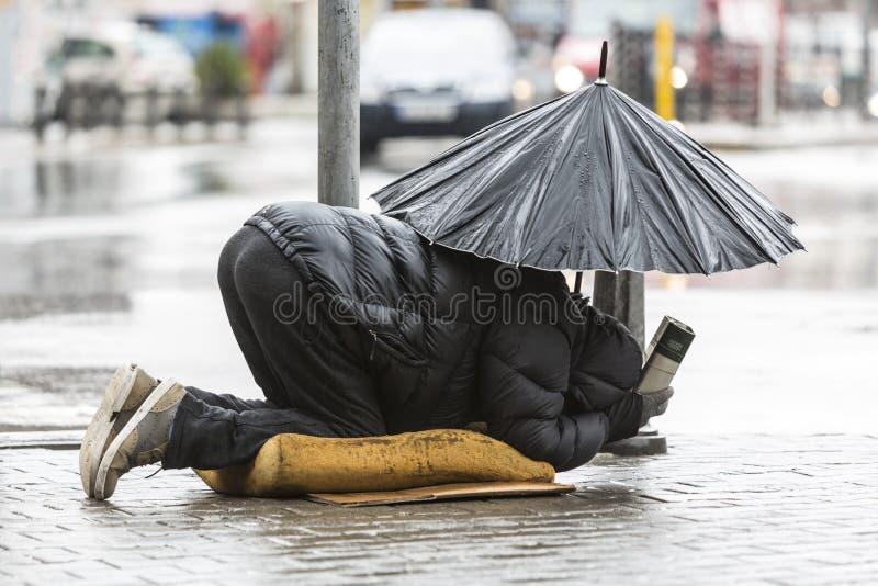 Mendicante senza tetto con l'ombrello nella pioggia immagini stock libere da diritti