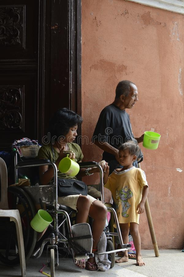 Mendicante sulla sedia a rotelle accanto all'uomo cieco che elemosina al portale del portone della porta della chiesa fotografie stock
