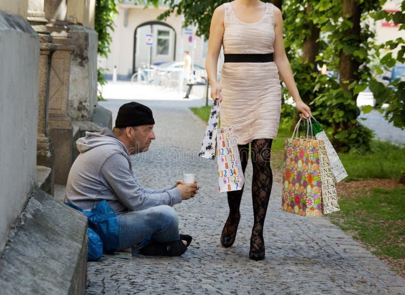 Mendicanti e donna ricca con i sacchetti di acquisto immagini stock