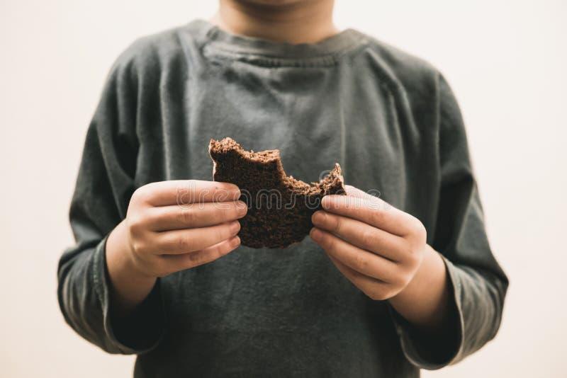 Mendigo da criança que come o pão barato Conceito pobre dos voluntários das doações das crianças e dos povos fotos de stock