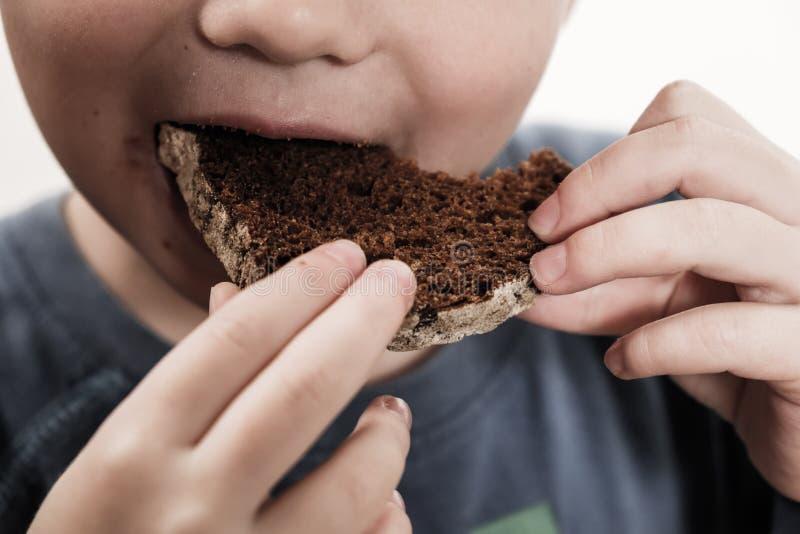 Mendigo del niño que come el pan barato Concepto pobre de los voluntarios de las donaciones de los niños y de la gente foto de archivo libre de regalías