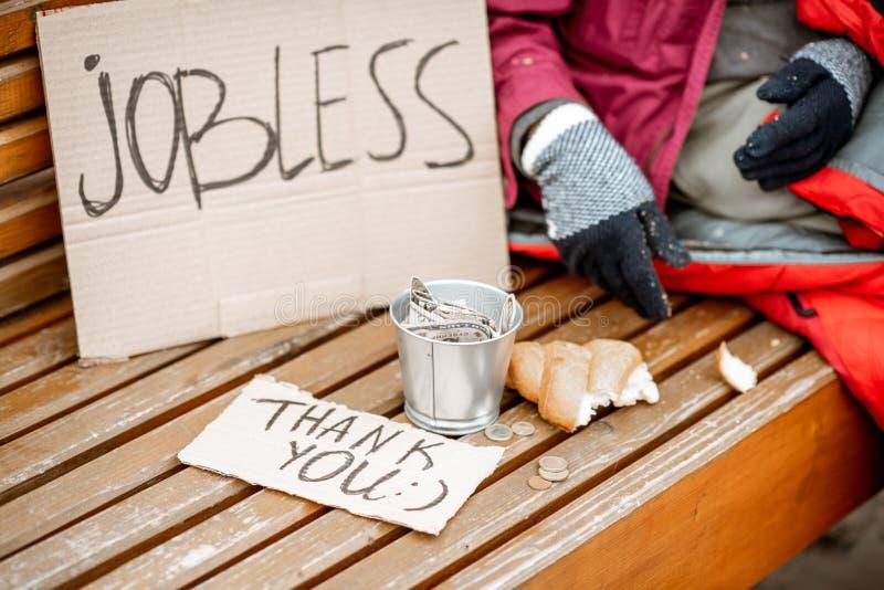 Mendigo desempleado que pide el dinero con cartulina y la taza foto de archivo libre de regalías
