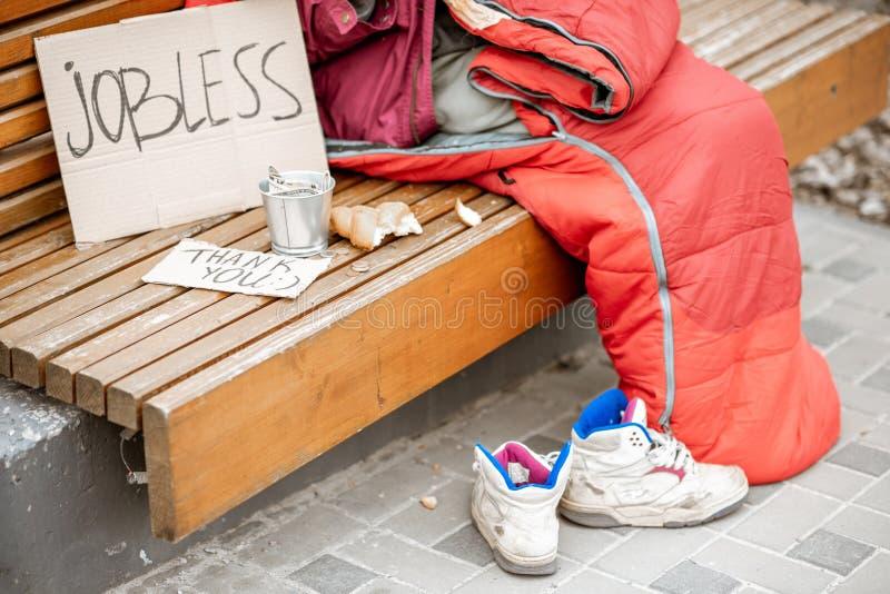 Mendigo desempleado que pide el dinero con cartulina y la taza imagen de archivo