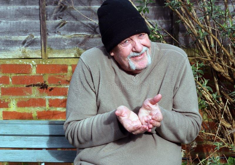 Mendigo mayor llevando a cabo hacia fuera ambo la mano. imagen de archivo libre de regalías
