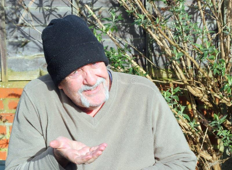 Mendigo mayor que lleva a cabo hacia fuera su mano. fotos de archivo libres de regalías