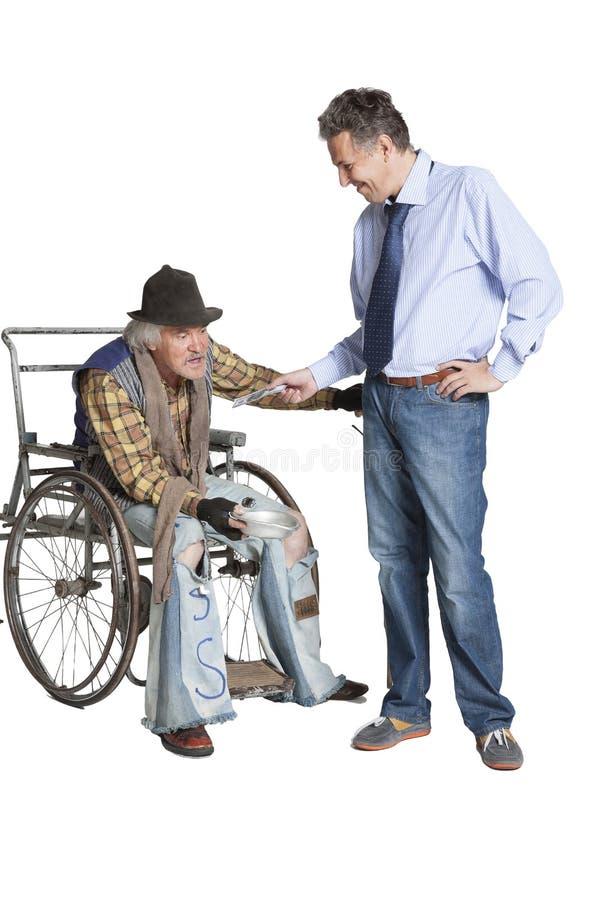 Mendigo que pide limosnas mientras que se sienta en una silla de ruedas fotografía de archivo libre de regalías