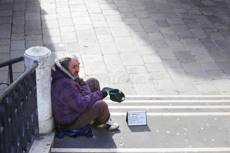Mendigo que senta-se em escadas em Veneza foto de stock