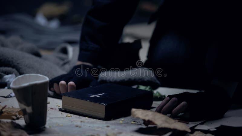 Mendigo sin hogar que se sienta en piso con la biblia y que ruega para la ayuda, firme convicci?n fotografía de archivo