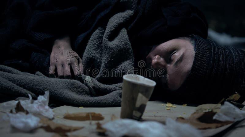 Mendigo sucio enfermo que duerme en la calle, la taza de papel pr?xima, la caridad y la donaci?n imagen de archivo libre de regalías