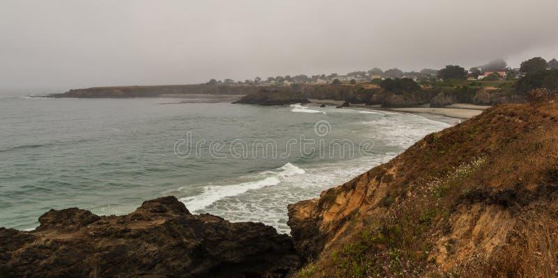 Mendocino加利福尼亚镇有雾、海滩、峭壁和波浪的从远方 免版税库存图片