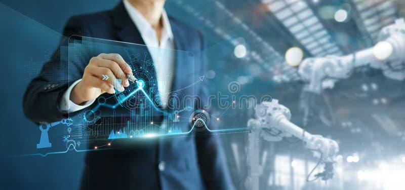 Menedżer inżyniera analizuje i kontroluje maszynę do automatyzacji zbrojeń robotów na oprogramowaniu nowoczesne dane interfejsu w obraz royalty free