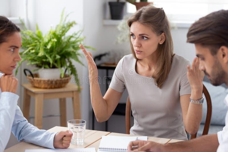Meneur d'équipe mécontent parlant avec des collègues discutant l'échouer photographie stock